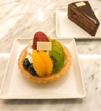 Fruit tart and piece of chocolate cake on marble table. In dessert cafe Royalty Free Stock Photography