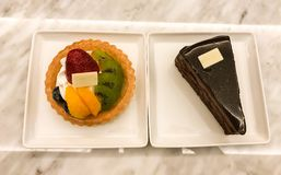 Fruit tart and piece of chocolate cake on marble table. In sweet shop Stock Photo