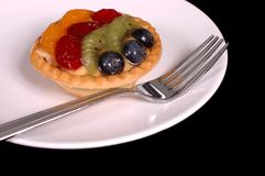 Fruit tart on plate 2. Fruit tart on white plate with fork Royalty Free Stock Photography