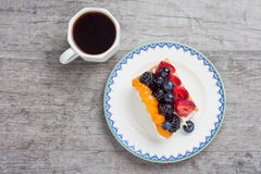 Fruit tart on plate served with coffee Royalty Free Stock Image