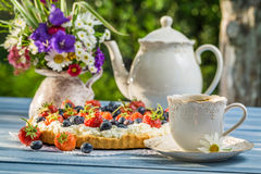 Fruit tart served with coffee in the summer garden Stock Photo