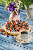 Fruit tart served with coffee in the summer garden Stock Photography