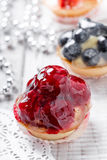 Fruit tarts with berries and strawberry on light background close up. Delicious dessert and candy bar Stock Photo