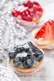 Fruit tarts with berries and strawberry on light background close up. Delicious dessert and candy bar Stock Photography
