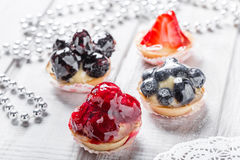 Fruit tarts with berries and strawberry on light background close up. Delicious dessert and candy bar Royalty Free Stock Photos