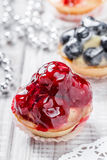 Fruit tarts with berries and strawberry on light background close up. Delicious dessert and candy bar. Royalty Free Stock Image