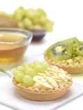Fruit tarts and tea. A dessert made of biscuit tart,cream and fruit,covered by almonds and pistachios royalty free stock image