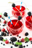 Fruit tea with blackberry, blueberry and raspberry decorated mint leaves on wooden desk. Selective focus stock photography
