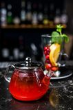 Fruit tea with cranberries, teapot and glass, dark background. stock photo