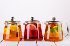 Fruit tea in glass jugs or jars with and lemon on the wooden table. Royalty Free Stock Image