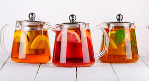 Fruit tea in glass jugs or jars with and lemon on the wooden table. Stock Photos