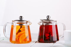 Fruit tea in glass jugs or jars with and lemon on the wooden table. Stock Photo
