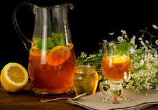 Fruit tea with lemon. Medicinal plants and honey,before black background with white flowers royalty free stock photography