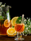 Fruit tea with lemon. Medicinal plants and honey,before black background with white flowers stock image