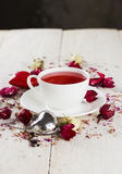 Fruit tea with a rose in a white cup. On a wooden background Royalty Free Stock Image