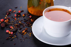 Fruit tea with slice of lemon. Mixture herbal floral fruit tea with petals, dry berries and fruits. Stock Photo