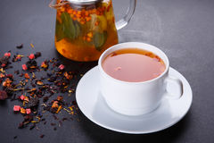 Fruit tea with slice of lemon. Mixture herbal floral fruit tea with petals, dry berries and fruits. Stock Photos
