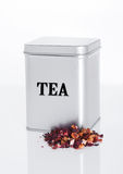 Fruit tea steel jar with loose tea next to it Royalty Free Stock Images