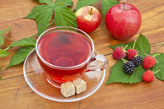 Fruit and tea with sugar. Apples, blackberries and raspberries on a green leaf and tea in glass cup and saucer with sugar lumps Royalty Free Stock Photography