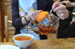 Fruit tea. Woman pours tea from glass teapot into a cup Royalty Free Stock Photos