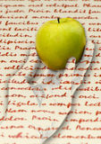 Fruit from the text. A human hand swells out from a text in the picture. This hand holds a green apple. The text is without copyright, it is created by a random Stock Photos