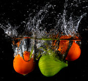 Fruit thrown in water Stock Photography