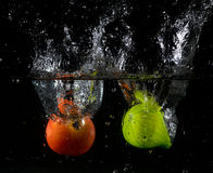 Fruit thrown in water Royalty Free Stock Image