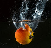 Fruit thrown in water Stock Images