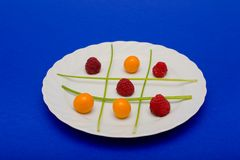 Fruit tic tac toe. Cape gooseberries, raspberries and parsel arranged on a plate to look like a game of tic tac toe. A clipping path is included for easy Royalty Free Stock Images