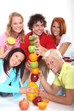 Fruit tower. Happy young people with fruits in studio Stock Photography