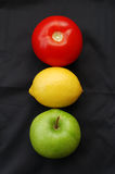 Fruit traffic light. Concept of fruits representing traffic light on black background (red = stop, yellow = caution, green = go Royalty Free Stock Image