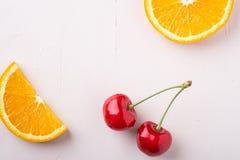 Fruit twee van de exemplaar ruimtezomer kersen met sinaasappelen op witte hoogste mening als achtergrond stock afbeeldingen