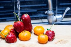 Fruit  under the pressure of water in the kitchen sink. Strawberry Tangerines and Rose apple  under the pressure of water in the kitchen sink Royalty Free Stock Images