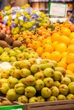 Fruit department with pears, oranges, coconuts and tangerines. Fruit, variety of fruit exposed inside a supermarket. In the foreground of pears, oranges royalty free stock photo