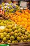 Fruit department with pears, oranges, coconuts and tangerines. Fruit, variety of fruit exposed inside a supermarket. In the foreground of pears, oranges royalty free stock images