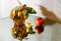Fruit in vase. Reflection in the mirror. Tangerines on a branch. Pomegranate. Apples. Tangerines on a branch with leaves. shadows on the wall stock image