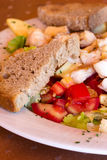Fruit-vegetable salad with chicken. And a piece of bread on a white plate Stock Images