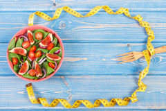 Fruit and vegetable salad, fork with tape measure, slimming and nutrition concept, copy space for text on boards Royalty Free Stock Photography