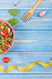 Fruit and vegetable salad, fork with tape measure, slimming and nutrition concept, copy space for text on boards Stock Photography