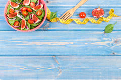 Fruit and vegetable salad, fork with tape measure, slimming and nutrition concept, copy space for text on boards. Fruit and vegetable salad in bowl and wooden Stock Image