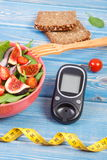 Fruit and vegetable salad and glucometer with tape measure, concept of diabetes, slimming and healthy nutrition. Fruit and vegetable salad, glucose meter for Royalty Free Stock Photography