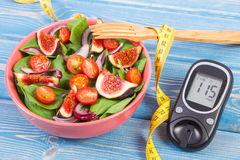 Fruit and vegetable salad and glucometer with tape measure, concept of diabetes, slimming and healthy nutrition Stock Image
