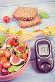 Fruit and vegetable salad and glucometer with tape measure, concept of diabetes, slimming and healthy nutrition. Fruit and vegetable salad, glucose meter with Stock Photo