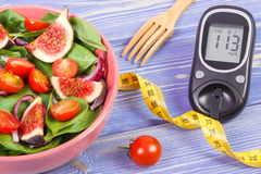 Fruit and vegetable salad and glucose meter with tape measure, concept of diabetes, slimming and healthy nutrition Royalty Free Stock Images