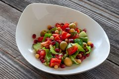 Fruit and vegetable salad: olives, pomegranate seeds, sweet peppers, corn, sprouted seeds and lettuce leaves. royalty free stock image