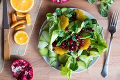Fruit and vegetable salad on a wooden table, top view. Vegetable salad on a plate - lettuce, corn salad, cucumber, avocado, orange, pomegranate. Top view stock image