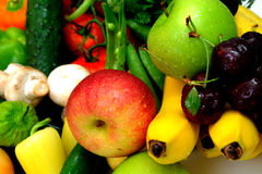 Fruit And Vegetables. Assorted fresh fruit and vegetables with a fuji and green apple in the foreground Royalty Free Stock Images