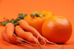 Fruit and Vegetables. A fresh orange pepper on an orange background with an orange and some carrots Stock Image