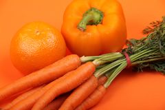 Fruit and Vegetables. A fresh orange pepper on an orange background with an orange and some carrots Royalty Free Stock Image