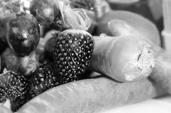 Fruit and vegetables. Black and white photo. A black and white photo of some fruit with strawberries, carrots and some kiwis royalty free stock photos